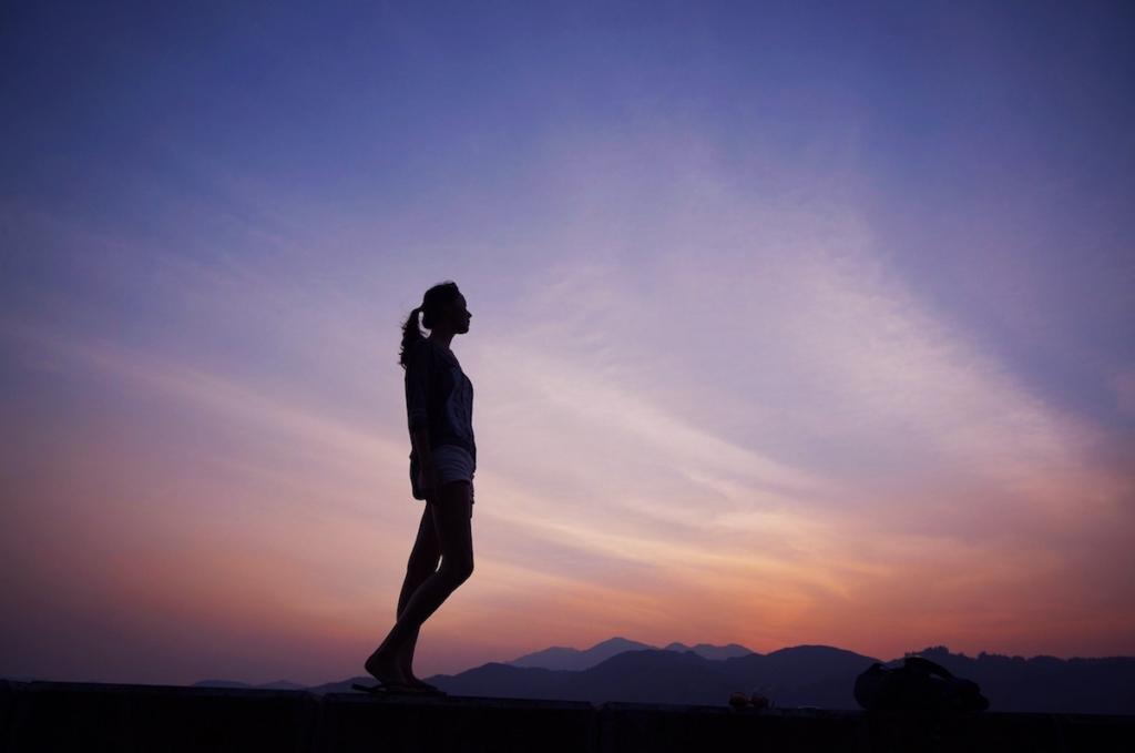 Femme regardant le soleil couchant