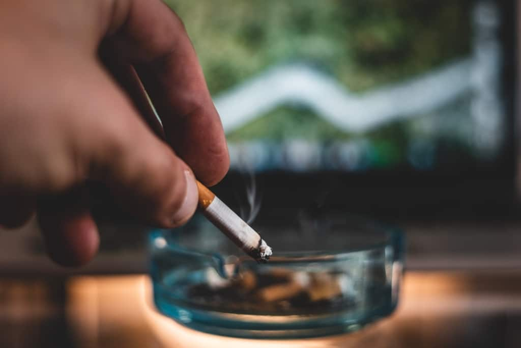 Fumeur écrasant sa cigarette dans un cendrier