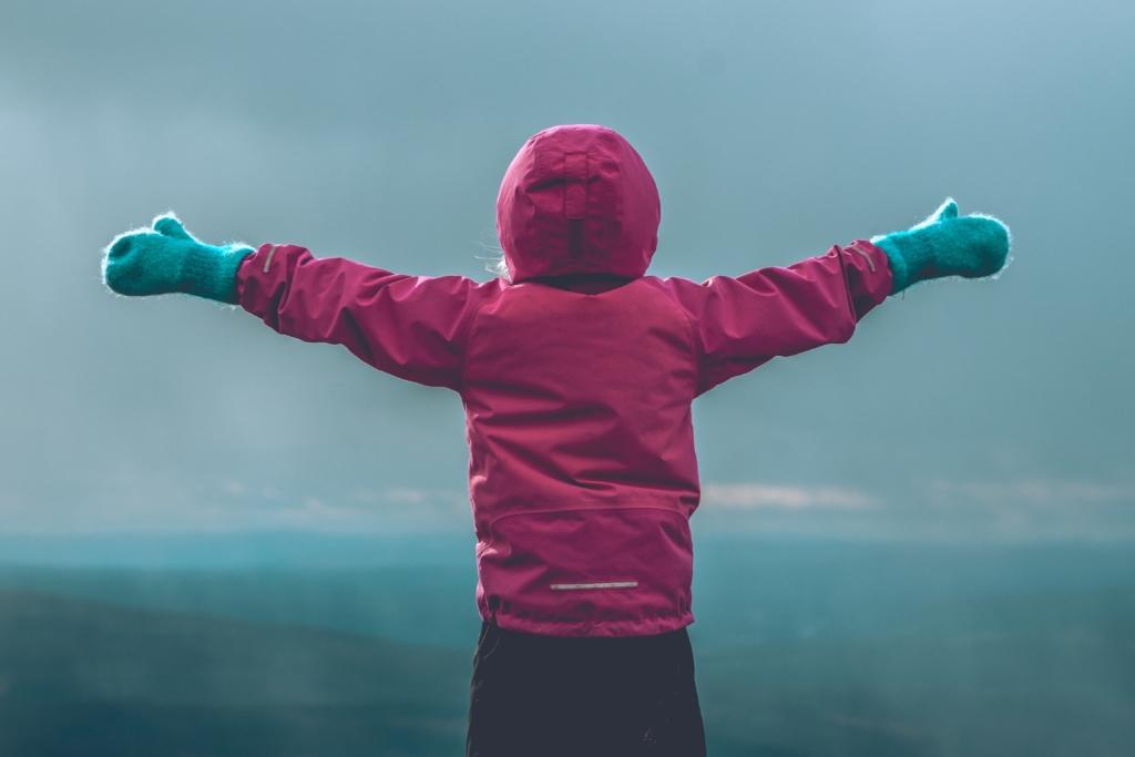 Enfant ouvrant les bras face à un massif montagneux
