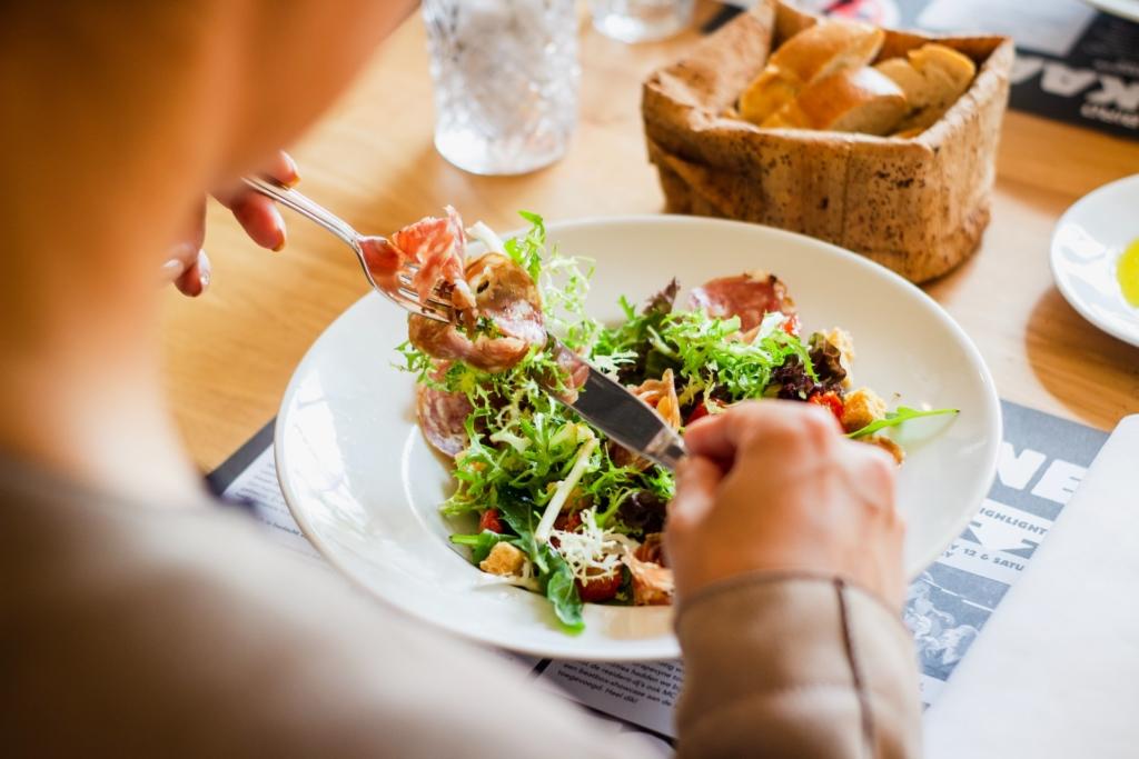 Personne mangeant une salade verte et charcuterie