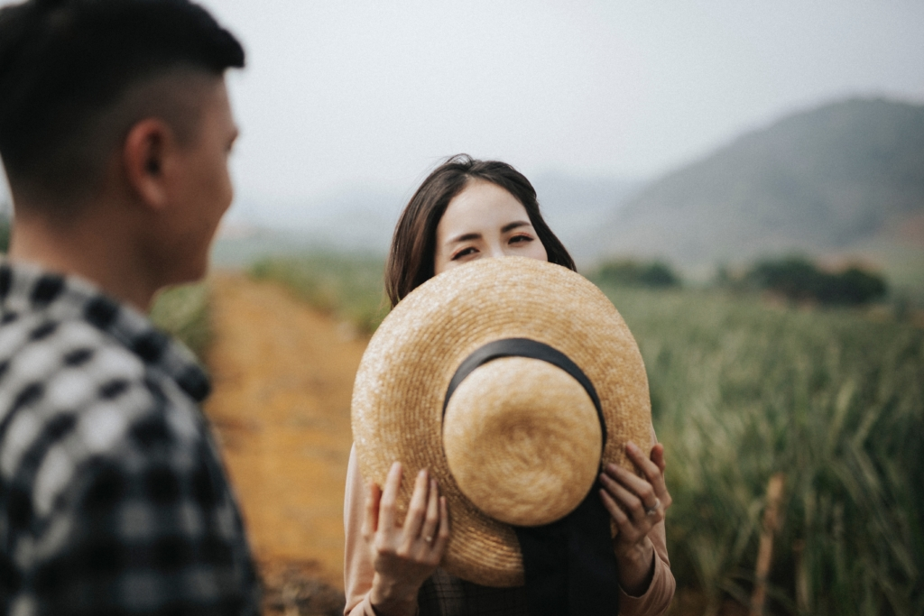 Femme se cachant derrière un chapeau