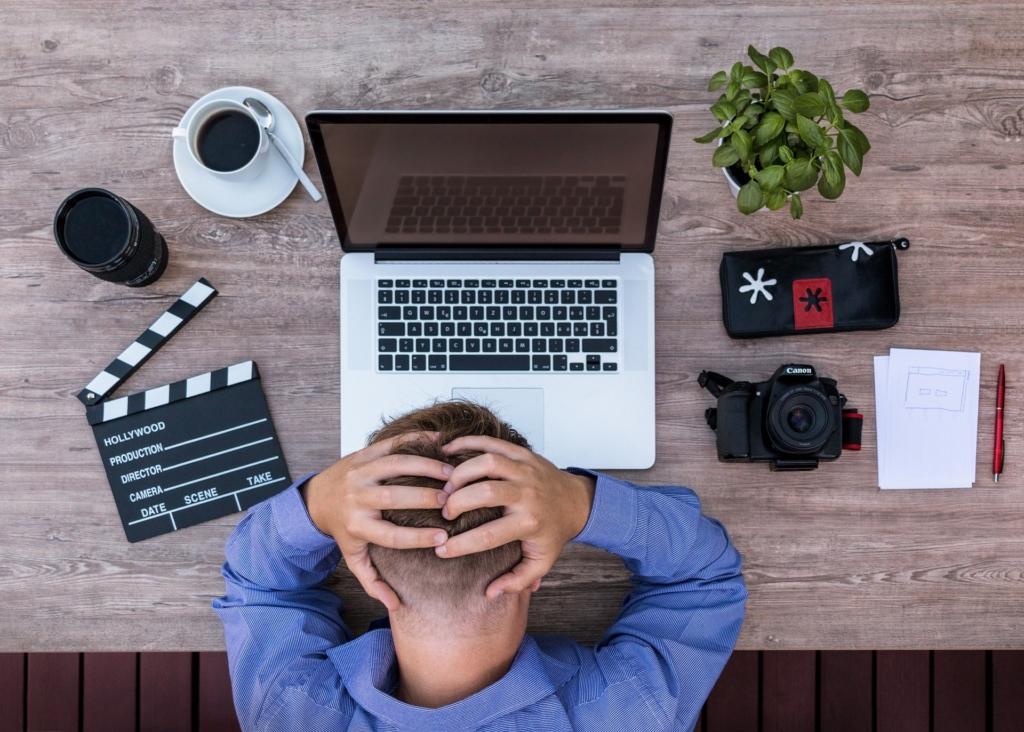 Homme prenant sa tête dans ses mains devant son ordinateur
